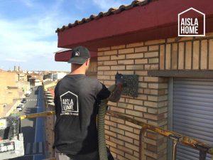Técnico trabajando en insuflado de lana de roca en fachada por el exterior (Corella, Navarra)